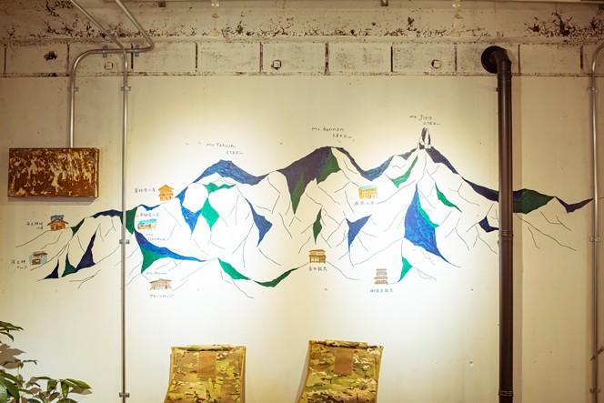 壁面いっぱいに描かれた鳳凰三山がどんと構える1Fの談笑スペース