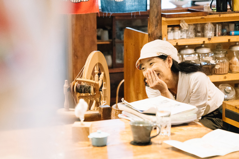 京子さん(左)と、糸紡ぎで使う糸車(中央)