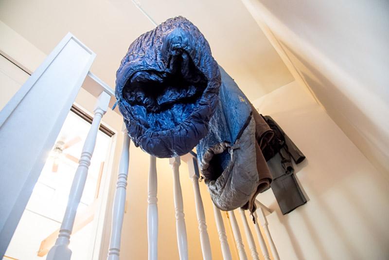 1階と2階をつなぐ階段の天井にはつっ張り棒を利用し、かさばるシュラフを干している。収納袋に入れないことでロフトも潰れず一石二鳥の収納方法に。