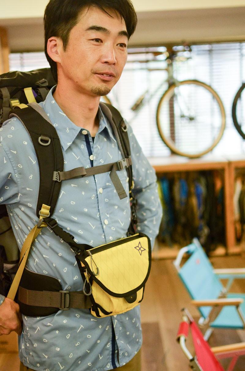(株)パーゴワークス代表の斎藤徹さん。黄色のチェストバッグがこの春リリースされた4WAY仕様の「スイング(M)」