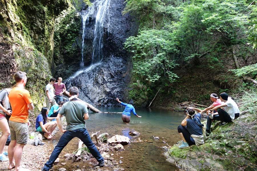 滝を前にしてはしゃぐ高校生たち