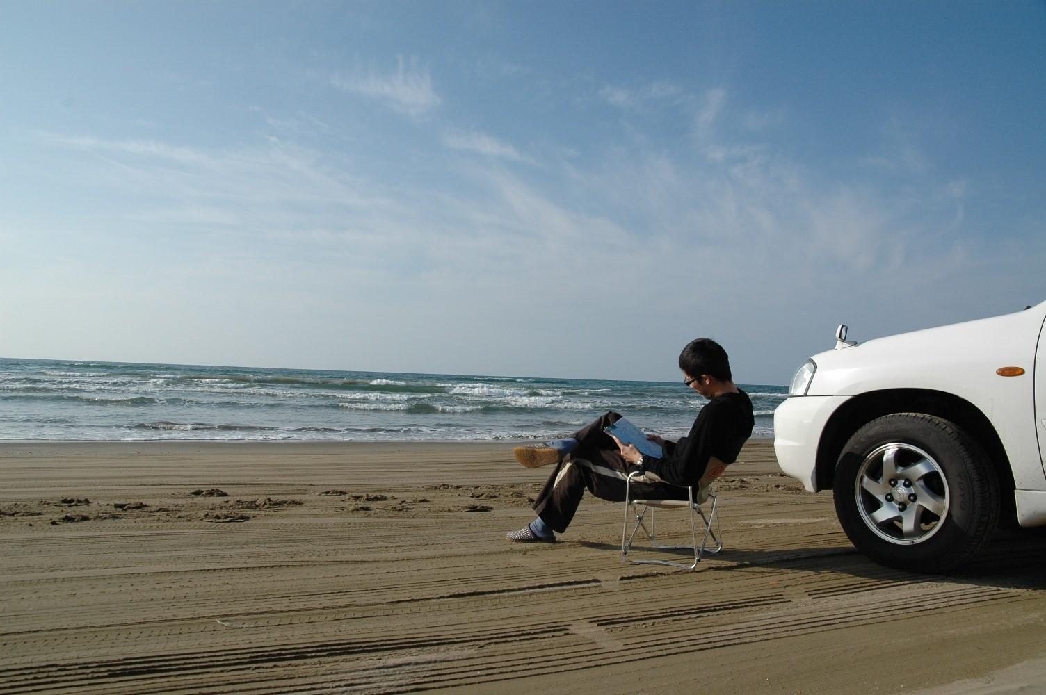 日本一周の途中で立ち寄った石川県の千里浜にて。当時はナビがなく、地図でルート確認しながら進んだそう(画像提供/ウッドさん)