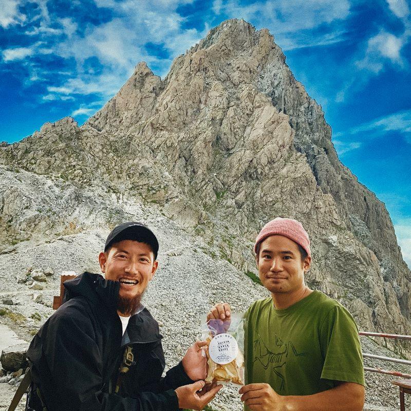 槍ヶ岳山荘の穂苅大輔さんに初期の乾燥りんごAPPLE CHIPSを手渡す