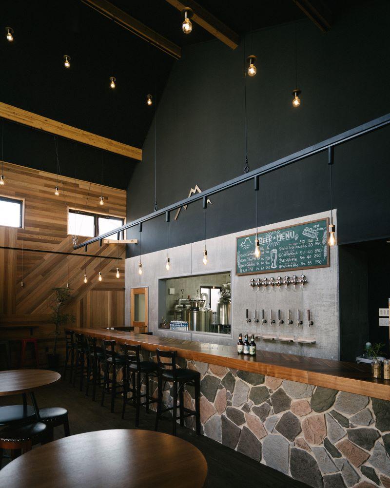 奥の醸造所とバーの間にカウンターがあるシンプルな作りの店内