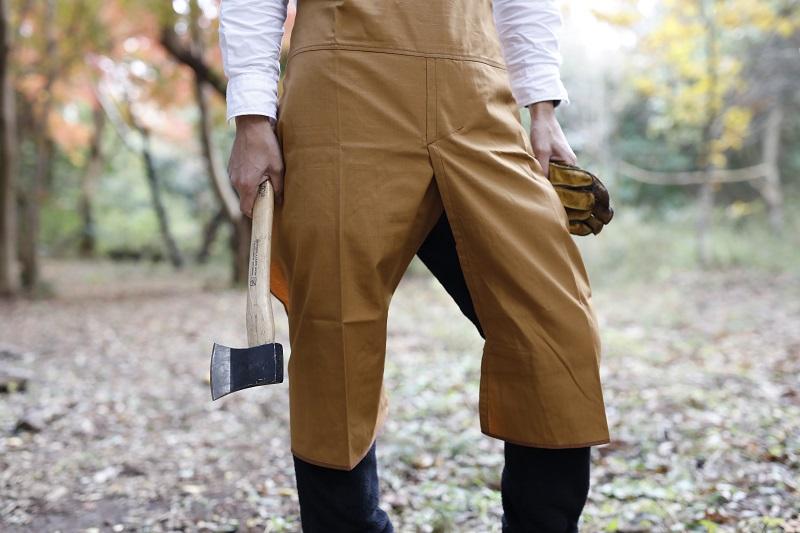 前かけ部分が割れていて、ベルクロで両足に巻き付けられるので、可動がスムーズに。膝をつくことが多いアウトドアシーンでも、パンツが汚れることがない。