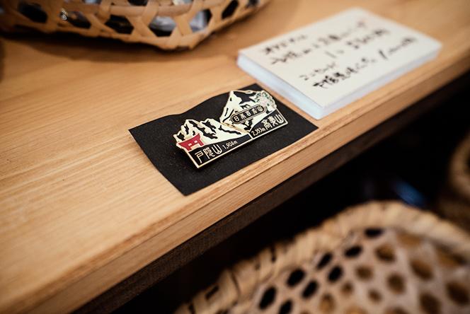 店内で販売されている登山記念ピンバッチも功さんオリジナル
