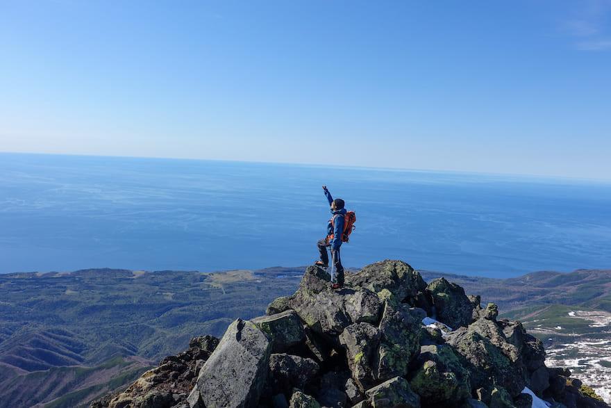 羅臼岳 オホーツク海をバックに太陽に手をかざすコスギ
